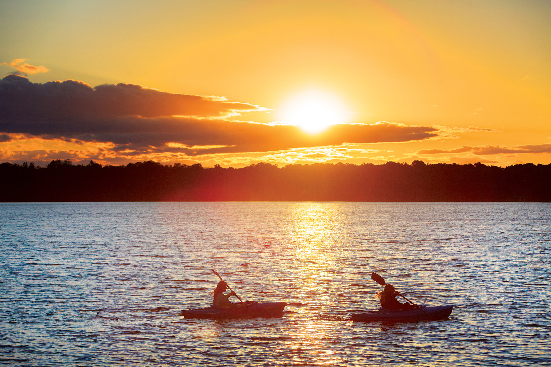Two canoers paddling on the lake at sunset